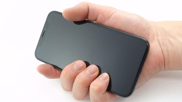 iPhone Xを握る手